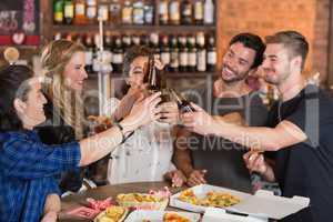 Happy friends toasting beer bottles over pizzas on table