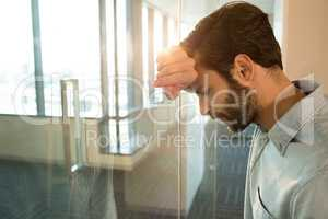 Depressed businessman leaning on glass