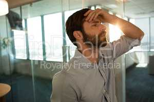 Sad businessman leaning on glass