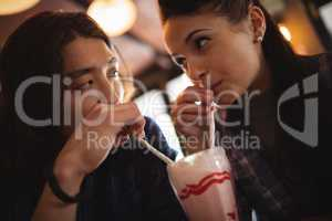 Close-up of couple having milkshake