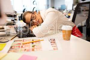 Tired businesswoman napping in creative office
