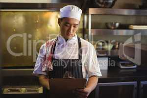 Chef writing on a clipboard