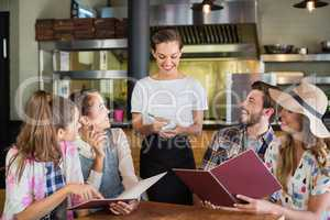 Waitress writing orders of customers in restaurant