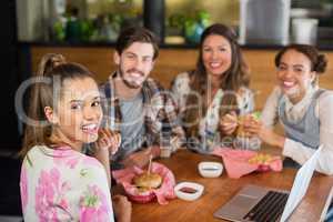 Happy friends having burger in restaurant
