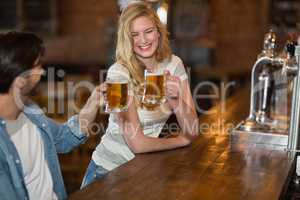 Young woman toasting beer with male friend at pub