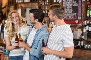 Friends holding beer bottles at pub