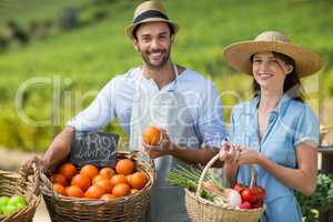 Smiling man and woman standing by fresh vegetables at farmer market