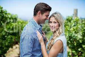 Side view of happy young couple embracing at vineyard