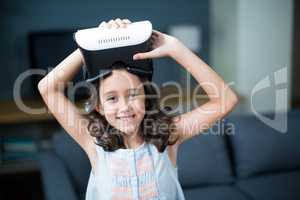 Portrait of girl holding virtual reality headset in living room