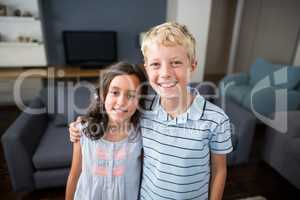 Siblings standing with arm around in living room