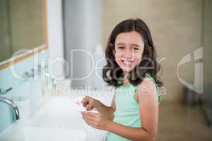 Girl putting toothpaste on brush in bathroom