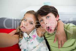 Siblings pulling funny faces in living room