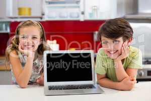 Smiling siblings with laptop on worktop in kitchen