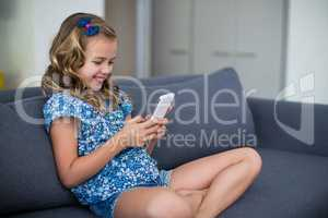Happy girl sitting on sofa and using mobile phone in living room