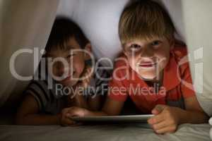 Portrait of siblings under bed sheet using digital tablet on bed