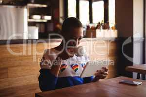Woman using digital tablet while drinking coffee