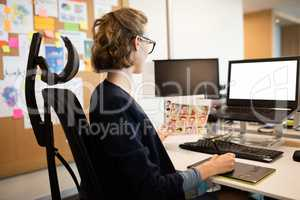 Businesswoman working on digitizer at desk
