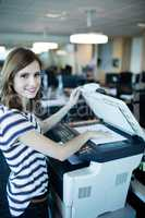 Portrait of businesswoman using copy machine in office