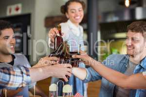 Young friends toasting beer bottles in pub