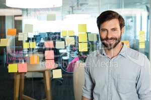 Portrait of young confident businessman standing by strategy on glass at office