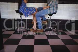 Low section of couple sitting on bar stool