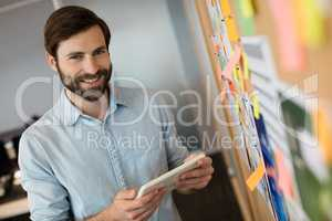 Portrait of young businessman holding digital tablet by soft board