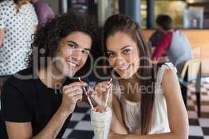 Portrait of smiling couple having drink in restaurant
