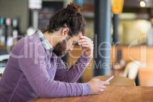 Depressed man holding mobile phone in restaurant