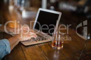 Cropped hands using laptop by beer glass at pub