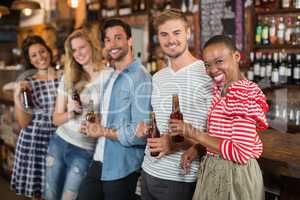 Cheerful friends with beer bottles at pub