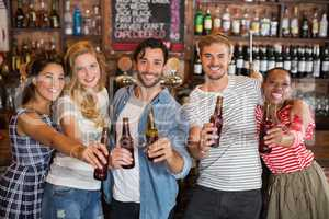 Cheerful friends holding beer bottles at pub