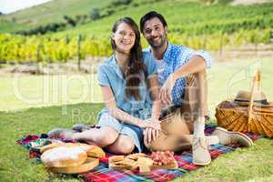Portrait of happy couple sitting on picnic blanket