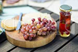 Grapes with cheese by jar on wooden table