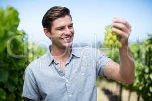 Happy young man holding grapes