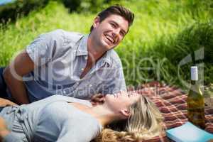 Cheerful young couple enjoying while lying on blanket