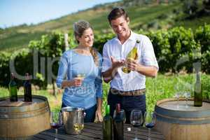 Man showing wine bottle to woman while standing by table