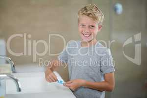 Portrait of boy putting toothpaste on brush in bathroom