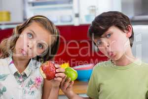 Siblings holding apple and pulling funny faces in kitchen