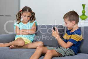 Upset girl sitting on sofa while boy using mobile phone in living room