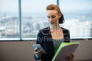 Businesswoman using mobile phone while holding files