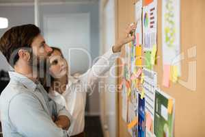 Young businessman with female colleague analyzing charts at office