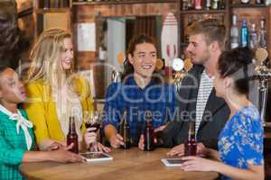 Young friends talking while standing by digital tablets and beer bottles in pub
