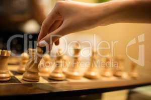 Cropped hand of businesswoman playing chess