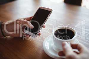 Hands of man using mobile phone while having coffee
