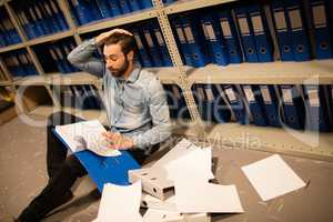 Tired businessman with scattered papers in file storage room