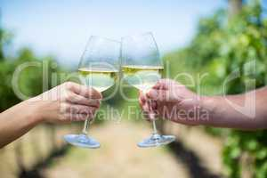 Cropped hands of couple toasting wineglasses