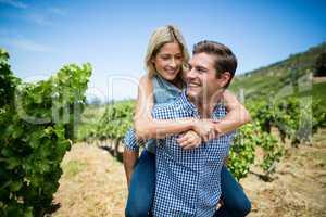 Smiling young couple piggybacking at vineyard