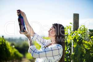 Side view of woman holding wine bottle at vineyard