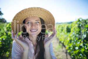 Portrait of beautiful young woman wearing hat on sunny day at vineyard