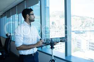 Businessman holding binoculars by glass window
